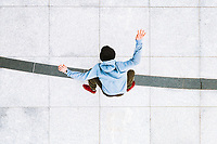 Aerial view of professional skateboarder doing a kick flip trick in urban background in central square in Kaunas city, Lithuania.