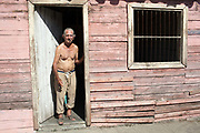 Old Cuban man with no shirt on with a cigar in his mouth, standing in the doorway of his basic pink wooden house, Palmira village in Cienfuegos province, Cuba.