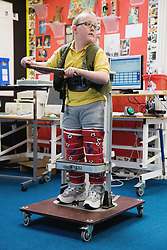 Physically disabled child using a supporting frame,