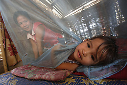 Lang and her family sleep under mosquito nets which are dipped by the local clinic, twice a year. <br /> Lang is 5 years old today, January 16th 2010.  Lang's mother Bounlid was photographed in the 6 months before giving birth and each year for the following 5 years following the birth, for the WHO Great Expectations project. <br /> Huey Kham Village, Santhong District, Vientiane Province, Lao PDR