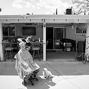 A hair dresser trying to make her rent works at a client's home after the salon she rents space from closed its doors as a non-essential business.