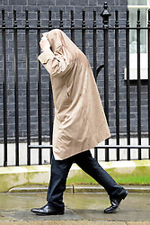 © Licensed to London News Pictures. 25/04/2012. Westminster, UK . A man walks up Downing Street with his coat over his head to avoid the rain. The Prime Minister David Cameron leaves Downing Street today 25 April 2012 for Prime Ministers Questions at the Houses of Parliament. Photo credit : Stephen Simpson/LNP