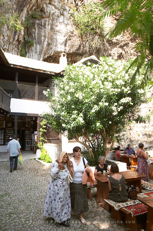 The court yard with cafe restaurant. An old Muslim woman in traditional clothes. The source of the Buna river and the house of the Whirling Dervishes, an old Muslim monastery, Blagaj. Federation Bosne i Hercegovine. Bosnia Herzegovina, Europe.