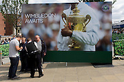 Day 2 of the annual lawn tennis championships and police officers question two men below a large champions trophy billboard, outside the mainline and underground (subway) station in the south London suburb. The Wimbledon Championships, the oldest tennis tournament in the world, have been held at the nearby All England Club since 1877.