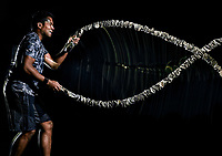 one afro american man exercising boot camp fitness ropes exercises isolated on black background with light painting speed effect