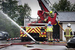 © Licensed to London News Pictures. 09/09/2019. London, UK. Seen from the back fire officers continue to pour water on a four-storey block of flats in Worcester Park, south-west London, where twenty fire engines and more than 100 firefighters were called overnight. The fire quickly spread at around 1.30am on Monday morning on Sherbrooke Way. No casualties are reported. Photo credit: Peter Macdiarmid/LNP