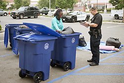 August 7, 2017 - Tustin, CA, USA - Using blue bins, officer Crouch helps Alena Clayton, 47, inventory her belongings for storage at the civic center in Tustin, CA on Monday, August 7, 2017. The city posted signs at the civic center telling people living in the homeless encampment that they must move out by 8 a.m. to make way for a temporary library. (Credit Image: © Ken Steinhardt/The Orange County Register via ZUMA Wire)
