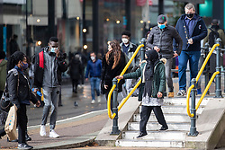 © Licensed to London News Pictures. 20/10/2020. Manchester, UK. People wearing face masks get on and off the tram platform on Market Street, Manchester. Manchester is expecting to be forced in to a Tier 3 lockdown unless a deal is agreed, which could see businesses such as pubs and bars closed. Photo credit: Kerry Elsworth/LNP