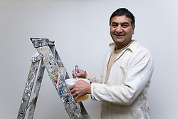 Decorator standing by his ladder; preparing wall paper paste,
