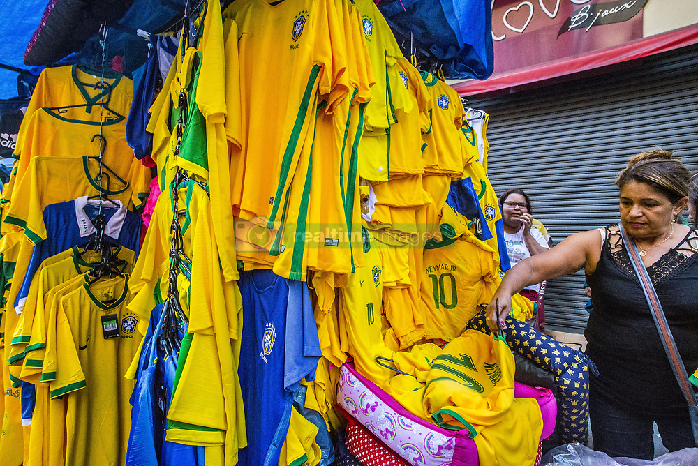 June 14, 2018 - Sao Paulo, Brazil - Shoppers pass on a street decorated in Brazilian flags ahead of the FIFA World Cup games in downtown Sao Paulo, Brazil. In a curious quirk of Brazil's electoral calendar, for the last 28 years Latin America's largest economy has gone to the polls shortly after the World Cup. In the football-obsessed country, politicians have long attempted to hijack the sport to burnish their image. (Credit Image: © Cris Faga via ZUMA Wire)