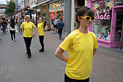 Four women in yellow t-shirts and sunglases perform an improvised dance on Carnaby Street in London, United Kingdom. Remaining totally silent, it was unclear as to the reason for the performance but appeared as a contemporary dance piece in public.