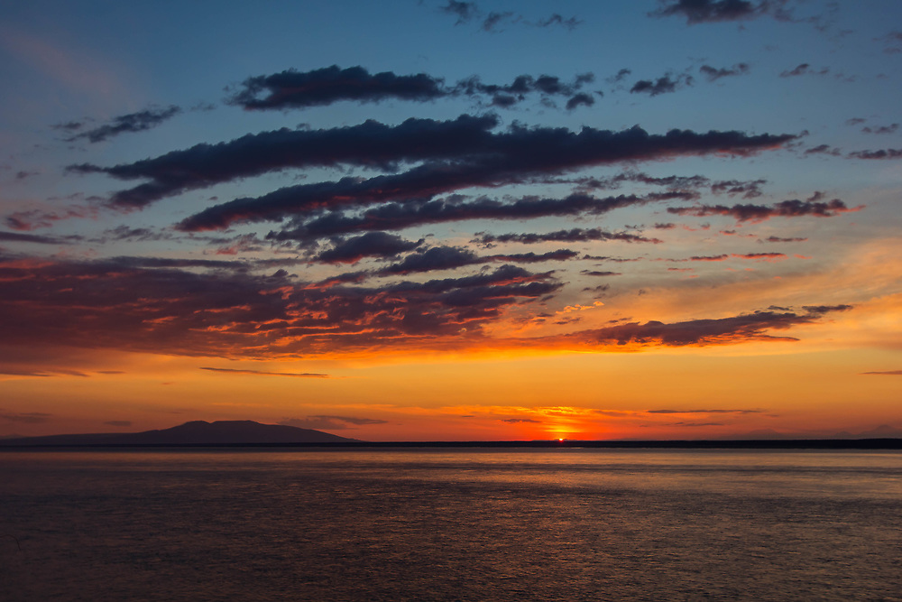 """Fiery sunset Kink Arm with Mount Susitna. Often referred to as Sleeping Lady because it looks like a woman laying down and many of us have gone our whole life thinking that was the native lore and that Susitna means sleeping lady. The mountain's Dena'ina name is Dghelishla, meaning """"Little Mountain""""; in English it was simply named for the Susitna River which means Sandy River."""