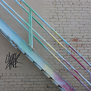Rainbow colored stairs outside a brick building with graffiti.