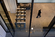 While office workers largely remain at home in accordance to government Covid guidelines and individual corporate policies, a solitary socially distanced company employee leaves through security barriers of his offices in the City of London, the capital's financial district, during the third lockdown of the Coronavirus pandemic, on 9th March 2021, in London, England.