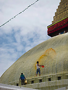 The giant Boudhanath stupa is being painted by cartkers polishing up the stupa for up coming religious events. The stupa is  part of Nepal's four UNESCO World Heritage Sites. The stupa is one of the most holy sites of pilgrimage for Buddhists around the world. Near Kahmandu, in the valley.