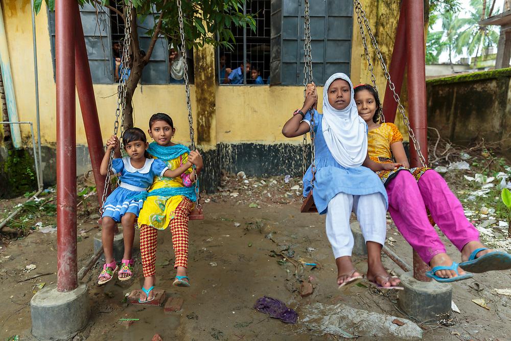 Before school begins, girls play on swings in the school playground