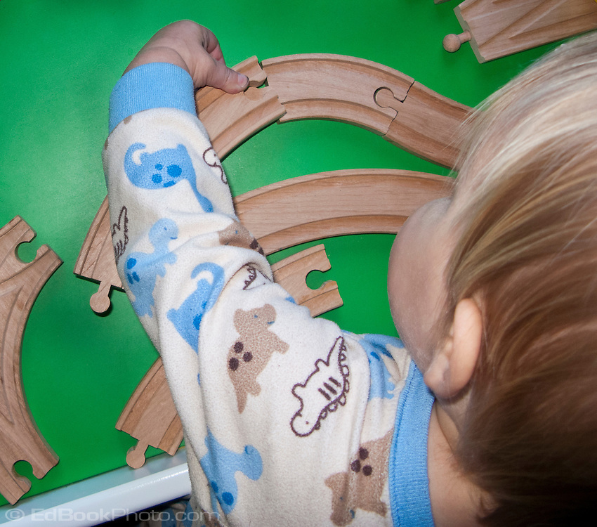 A toddler at constructive play learns how to join track together in a play learning situation.