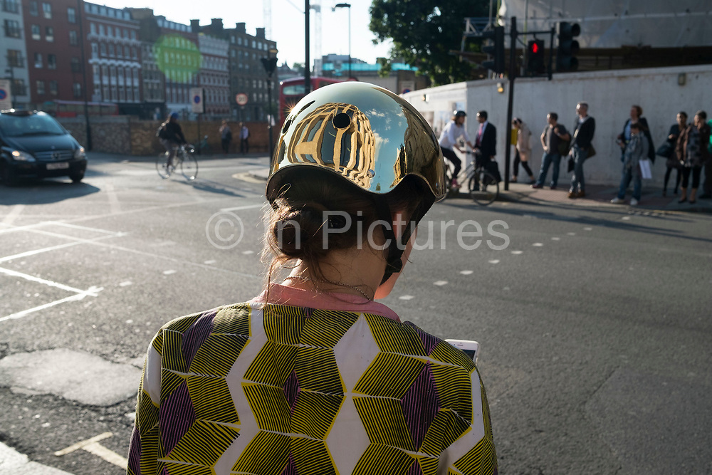 Female cyclist wearing a gold safety helmet stops to check her mobile phone in London, England, United Kingdom. A bicycle helmet is designed to attenuate impacts to the head of a cyclist in falls while minimizing side effects such as interference with peripheral vision.