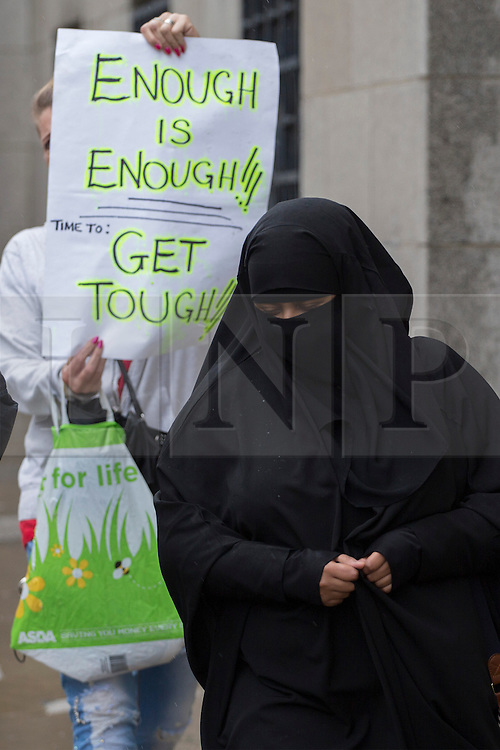 © licensed to London News Pictures. London, UK 16/08/2013. Right wing protesters hold banners when Ayan Hadi arriving to The Old Bailey Court in London on Friday, 16 August 2013. Hadi, 31, Richard Dart's wife pleaded guilty at the Old Bailey to failing to provide information that could have helped in securing the apprehension, prosecution or conviction of Dart for an offence involving an act of terrorism. Photo credit: Tolga Akmen/LNP