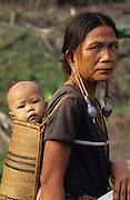 DAYAK, MALAYSIA. Sarawak, Borneo, South East Asia. Dayak, 'Kenyah', woman and child in papoose. Tropical rainforest and one of the world's richest, oldest eco-systems, flora and fauna, under threat from development, logging and deforestation. Home to indigenous Dayak native tribal peoples, farming by slash and burn cultivation, fishing and hunting wild boar. Home to the Penan, traditional nomadic hunter-gatherers, of whom only one thousand survive, eating roots, and hunting wild animals with blowpipes. Animists, Christians, they still practice traditional medicine from herbs and plants. Native people have mounted protests and blockades against logging concessions, many have been arrested and imprisoned.