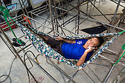 19 JANUARY 2014 - BANGKOK, THAILAND:  A truck driver for a traveling mor lam show rests in a hammock under the stage before the show in Khlong Tan Market in Bangkok. Mor Lam is a traditional Lao form of song in Laos and Isan (northeast Thailand). It is sometimes compared to American country music, song usually revolve around unrequited love, mor lam and the complexities of rural life. Mor Lam shows are an important part of festivals and fairs in rural Thailand. Mor lam has become very popular in Isan migrant communities in Bangkok. Once performed by bands and singers, live performances are now spectacles, involving several singers, a dance troupe and comedians. The dancers (or hang khreuang) in particular often wear fancy costumes, and singers go through several costume changes in the course of a performance. Prathom Bunteung Silp is one of the best known Mor Lam troupes in Thailand with more than 250 performers and a total crew of almost 300 people. The troupe has been performing for more 55 years. It forms every August and performs through June then breaks for the rainy season.              PHOTO BY JACK KURTZ