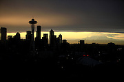 The sun peeks out at sunrise at Kerry Park in Seattle. Mount Rainier is illuminated in the background. (Erika Schultz / The Seattle Times)