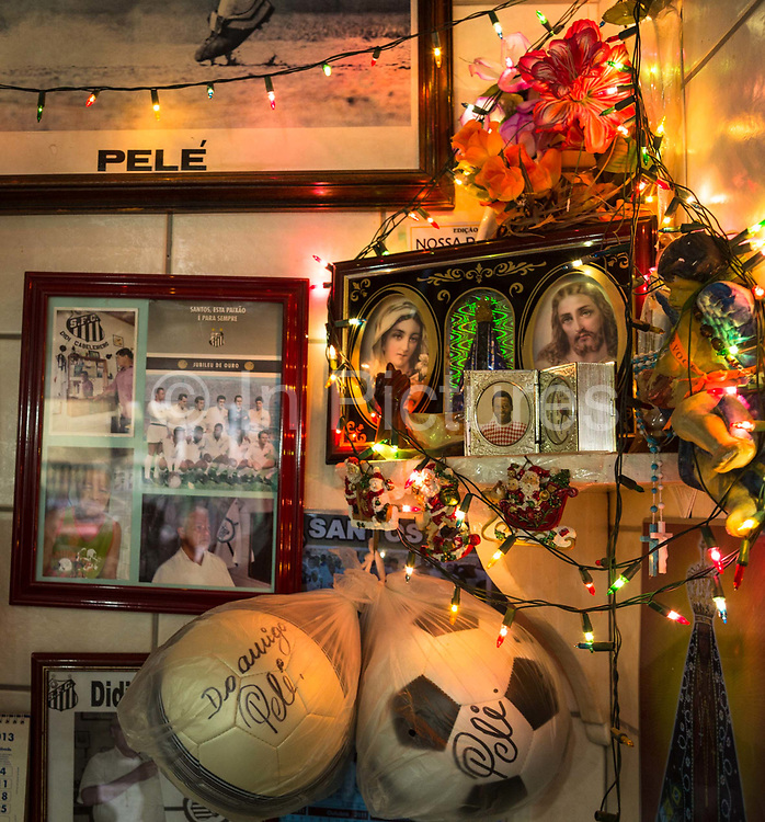 Inside Pele's modest and cramped barber's shop, the equally legendary barber Didi has been trimming Pele's hair since the young star's early years at Santos FC, over 45 years. This modest space, oposite Vila Belmiro Santos stadium  has an interior redolant with religious idolatry and is a temple to the living legend, Santos.