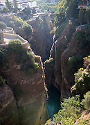El Tajo canyon of the Rio Guadalevin river with white buildings perched on the cliff top, Ronda, Spain
