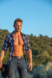 cowboy with open shirt at sunset
