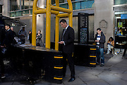 Yellow security gate scanners, still in place the day after Margaret Thatcher's ceremonial funeral at St Paul's Cathedral that required tight security, remains as a backdrop for commuting or waiting Londoners.