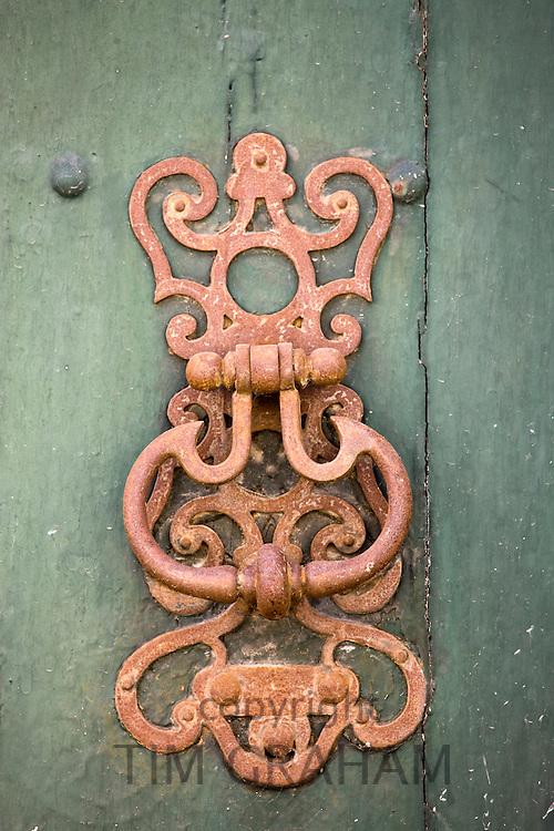 Door knocker design on green painted wooden door in Bourdeilles near Brantome, Northern Dordogne, France