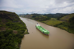 Green oil tanker traveling between terraced banks underway to the Panama Canal.