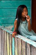 Girl sucks on a lollipop on her family's verandah in the Kampong Ayer (village on stilts).