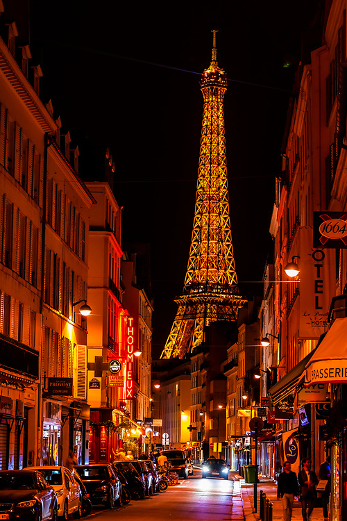 Rue St. Dominique with the Eiffel Tower behind.  The Eiffel Tower is the world famous wrought-iron lattice tower that is the most famous landmark of Paris, France.