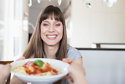 Portrait of woman with spaghetti plate, smiling