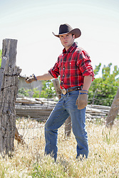 hot working cowboy by a wooden fence