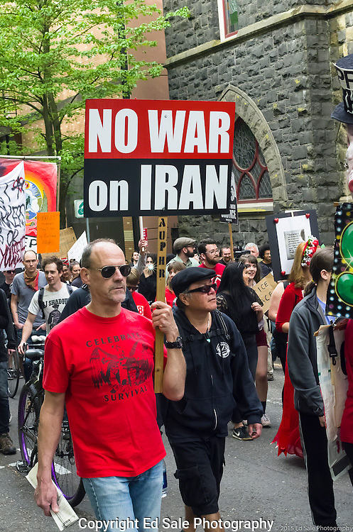 Demonstrator in 2015 May Day rally and march in Portland, Oregon holds sign saying No War on Iran