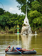 30 SEPTEMBER 2016 - SAI NOI, AYUTTHAYA, THAILAND: A man from the flooded village of Sai Noi rests on a home made raft near Wat Boonkannawas. The Chao Phraya River, the largest river that runs through central Thailand, has hit flood stage in several areas in Ayutthaya and Ang Thong provinces. Villages along the river are flooded and farms are losing their crops due to the flood. This is the same area that was devastated by floods in 2011, but the floods this year are not expected to be as severe. The floods are being fed by water released from upstream dams. The water is being released to make room for heavy rains expected in October.      PHOTO BY JACK KURTZ