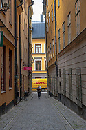 Stockholm, Sweden -- July 16, 2019. A man walks along a  side street  in Old Town, Stockholm; A delivery truck passes behind him.