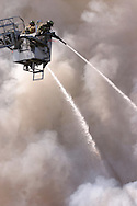 Goshen, N.Y. - Two firefighters on a ladder truck spray water on a fire that destroyed a two-story house on April 29, 2006. ©Tom Bushey