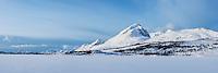 Ristind mountain peak rises above a snow covered lake Ostadvatnet, Vestvågøy, Lofoten Islands, Norway