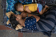 A 17-year-old Honduran mother seeking asylum and her 2-year-old son wait on the Mexican side of the Brownsville-Matamoros International Bridge after being denied entry by U.S. Customs and Border Protection officers near Brownsville, Texas, U.S., July 2, 2018.
