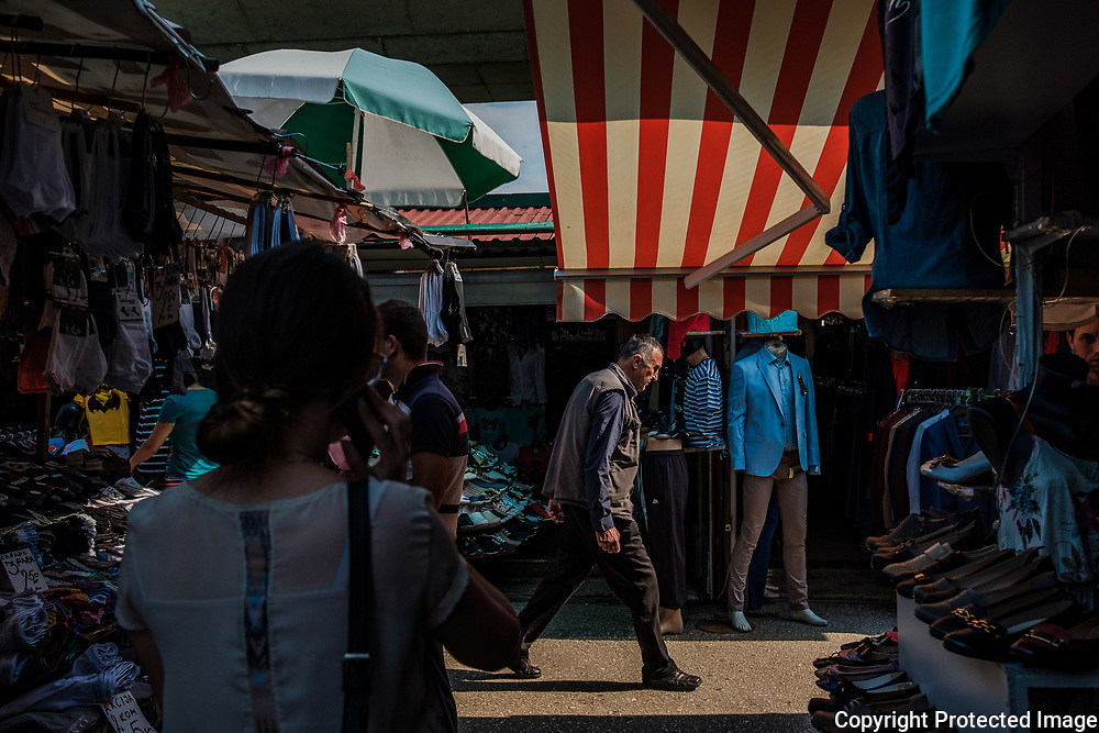 Locals walk through a day market set up near a freeway bridge outside of the city center. Sarajevo remains at the crossroads between modernizing and tradition.