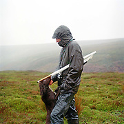 Beater with his dog on a grouse shoot, Bransdale, North York Moors, North Yorkshire, UK. Beaters use flags to drive the grouse towards the guns, who stand in shooting butts.