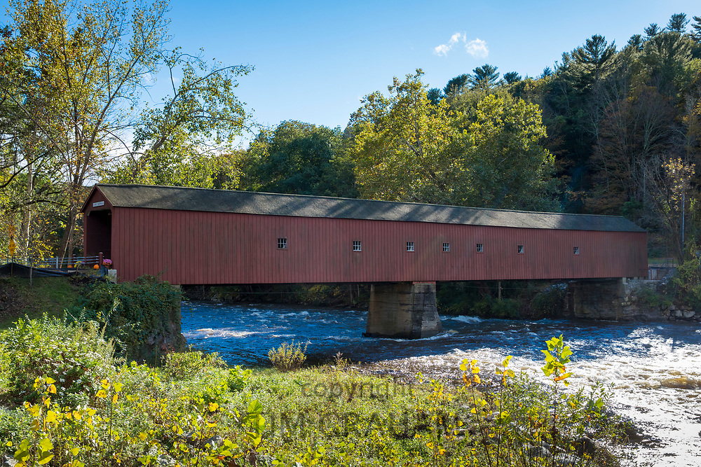 Side view of the wooden structure of West Cornwall covered bridge and Housatonic River during The Fall in Connecticut, USA