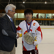 Jin Chen, China, receives the runners up plate award for the tournament from Kai Hietariinta, IIHF Tournament Chairman at the conclusion of the 2012 IIHF Ice Hockey World Championships Division 3 held at Dunedin Ice Stadium. Dunedin, Otago, New Zealand. 22nd January 2012. Photo Tim Clayton