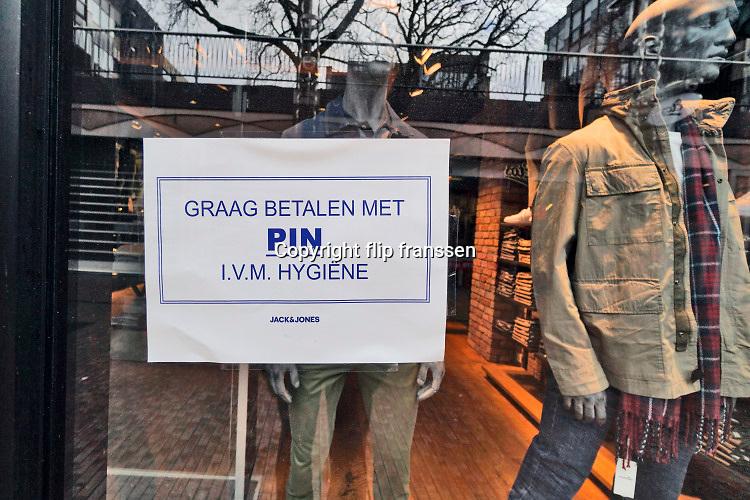 Nederland, Nijmegen, 13-3-2020 In de winkelstraten is het een stuk rustiger als normaal . Veel winkels hebben bij de ingang een mededeling die verwijst naar het handen schudden of afstand houden van het personeel naar de klant toe . Ook het verzoek te betalen met PIN ipv contant geld is op een raam geplakt.Foto: Flip Franssen