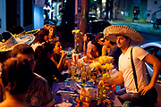 Man in sombrero with other people at table, eating dinner outside, Palermo, Buenos Aires, Federal District, Argentina.