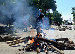 June 22, 2017 - Pulwama, Jammu and Kashmir, India - A young boy walks past the fire during protests against the Killing of Three Lashmar e Toiba (LeT) rebels in an overnight encounter in Kakapora Pukwama. The youth was identified Touseef Ahmad Wani, a resident of Tengpuna village of the district. (Credit Image: © Muzamil Mattooa/Pacific Press via ZUMA Wire)