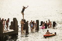 June 21, 2017 - Aberystwyth, UK. People in Aberystwyth cooling off by diving into the sea on yet another day of clear blue skies and searing heat on the west coast of Wales as the mini heat-wave continues over the British Isles. The Met Office has warned of heavy rain and thunderstorms with the chance of localised flooding affecting much of the UK in the next 24 hours as the weather system starts to break down after many days of record hight temperatures. (Credit Image: © Keith Morris/London News Pictures via ZUMA Wire)